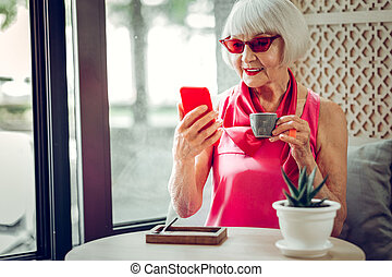 Nice pleasant aged woman sitting in the cafe