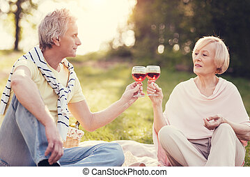 Nice pleasant couple cheering with wine