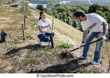 Nice pleasant man digging a hole