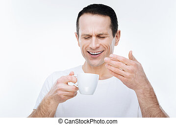Nice pleasant man smelling the aroma of coffee