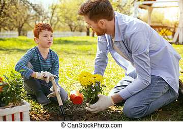 Nice pleasant man teaching his son