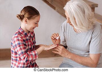 Nice pleasant woman holding a nail varnish brush