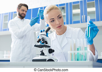 Nice pleasant woman holding a test tube