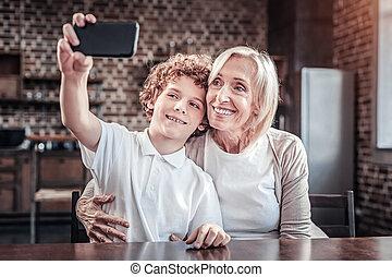 Nice positive boy holding his smartphone