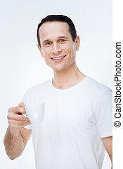 Nice positive man enjoying his coffee