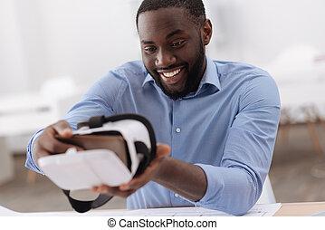 Nice positive man holding a smartphone