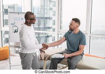 Nice positive men shaking hands