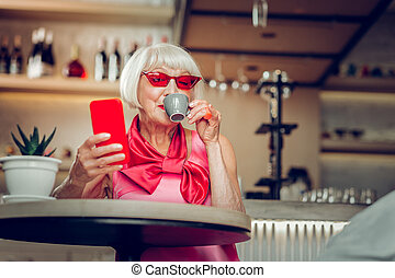 Nice positive senior woman enjoying her coffee