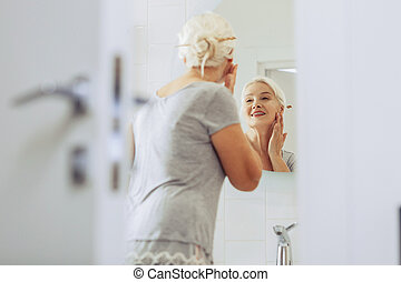 Nice positive senior woman touching her cheek