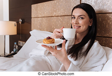 Nice positive woman enjoying her tea