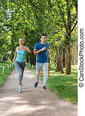 Nice positive young couple running outdoors together