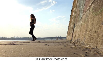 Nice Pregnant Woman in Black Suit Dances on Riverbank on a Sunny Day in Slo-Mo