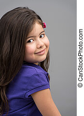 nice pretty girl sitting and smiling. small girl wearing purple t-shirt