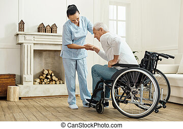Nice senior man getting out from the wheelchair - Medical...