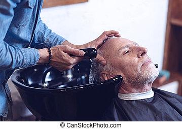 Nice senior man visiting a barbershop