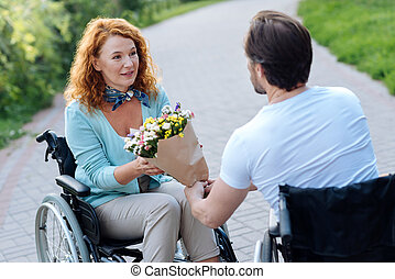 Nice senior wheelchaired woman getting a bunch of flowers