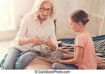 Nice senior woman showing her granddaughter how to knit