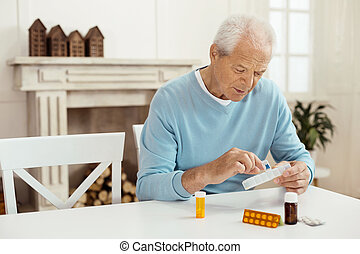 Nice serious man taking a pill