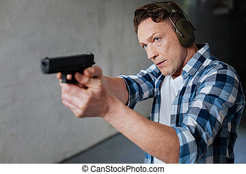 Nice serious man visiting the shooting range