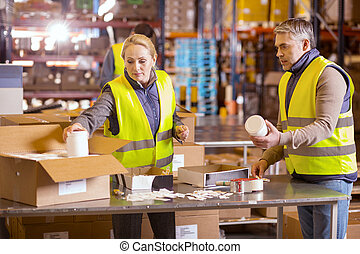 Nice serious people packing boxes