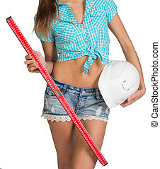 Nice sexy woman holding red building level and white helmet. In a cropped photo