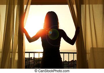 silhouette of a women near the window on hotel