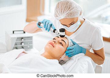 Nice skilled female dermatologist holding a dermatoscope