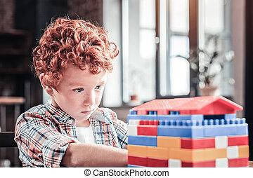 Nice smart boy building a house