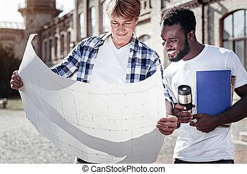 Nice smart students studying the blueprint