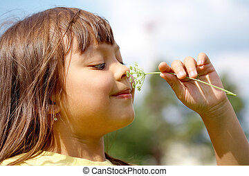 Nice smell - Portrait of little girl enjoying smell of ...