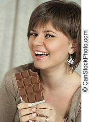 Nice smiling beautiful woman holding a chocolate bar
