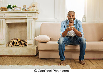 Nice smiling man relaxing on the couch