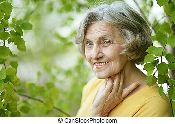 Nice smiling old woman on the green leaves background