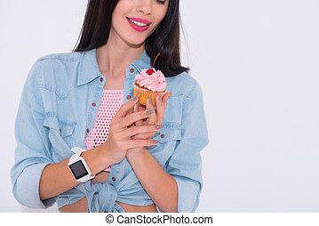 Nice smiling woman holding cupcake