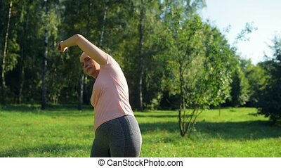 Nice sporty aged woman doing warm up exercises in the park