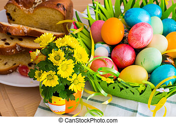 Nice spring yellow flowers, Easter eggs and traditional holiday cake