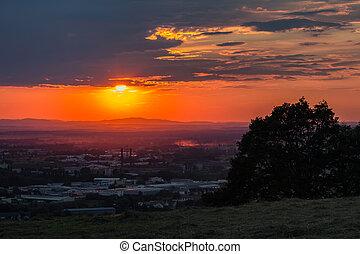Nice sunset over city Ceske Budejovice with tree silhouette