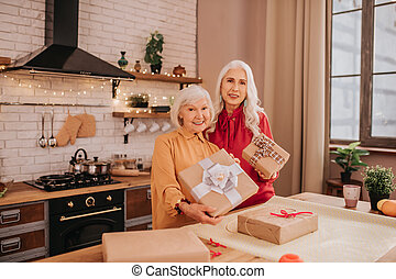Two senior good-looking ladies holding a gift and feeling great