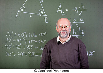 Nice teacher smiling at camera in his classroom
