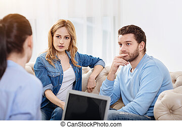 Nice thoughtful couple listening to the psychologist