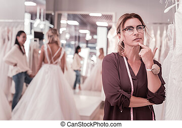 Nice thoughtful woman thinking about wedding dresses