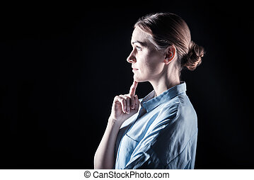 Serious look. Nice pleasant thoughtful woman touching her chin and looking in front of her while standing against black background