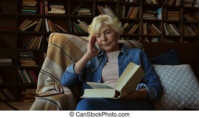 Nice tired senior woman reading a book