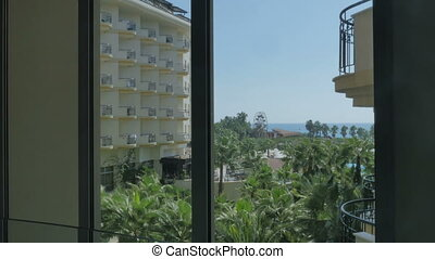 Nice view from the hotel window on the sea, palm trees. The girl takes a photo of the landscape from her room.