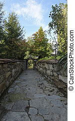 Nice view of the cobblestone road leading to the gate through the garden with a hedge in autumn