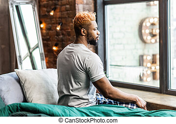 Pleasant African American man sitting in front of the window