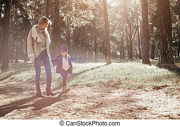 Nice walk with mom. A little curly girl is walking with her mother in forest
