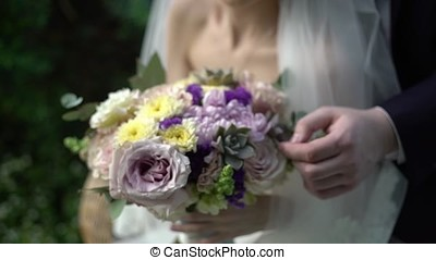 Nice wedding bouquet in bride's hand. Hands of the bride and groom with rings on a beautiful wedding bouquet