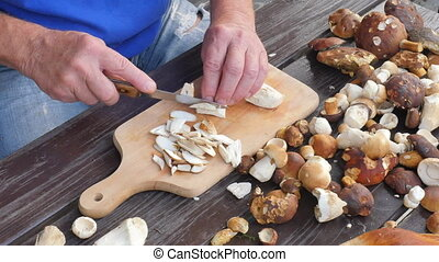 Nice wild mushrooms are cut with knife into small pieces on...