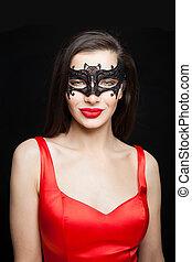 Nice woman fashion model in black mask smiling on dark background